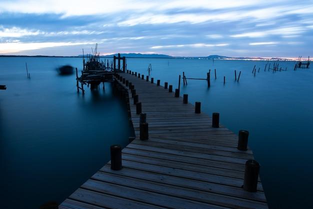 Molo Na Morzu Otoczone Wzgórzami Pod Zachmurzonym Niebem Wieczorem W Portugalii Darmowe Zdjęcia