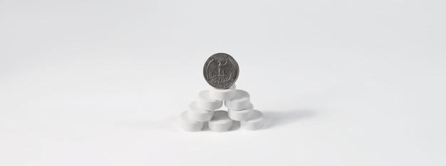 Moneta Stoi Na Górze Tabletek, Na Białym Tle Na Białym Tle, Kopia Przestrzeń. Premium Zdjęcia