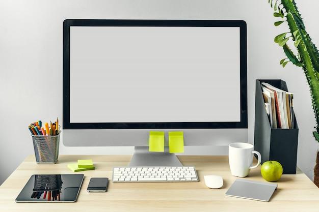 Monitor komputerowy z białym ekranem makiety na stole w biurze z materiałami eksploatacyjnymi Premium Zdjęcia