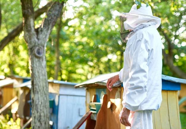 Monochromatyczny Portret Starszego Mężczyzny Ubrany W Garnitur Pszczelarski Pozowanie Na Jego Pasieki W Ogrodzie Copyspace Zawód Zawód Rolnik Rolnik Praca Hobby Koncepcja Stylu życia. Darmowe Zdjęcia