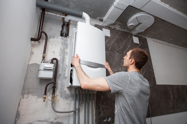 Montaż i ustawienie nowego kotła gazowego na ciepłą wodę i ogrzewanie. Premium Zdjęcia