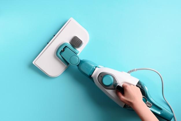 Mop do czyszczenia parą na niebieskim tle. Premium Zdjęcia