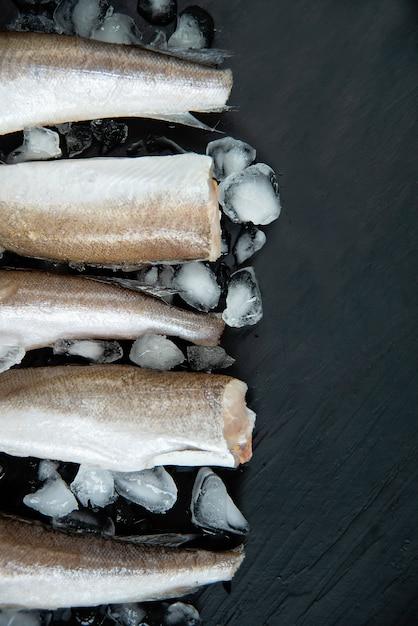 Morszczuk Z Surowej Ryby. Pięć Filetów Z Surowej Ryby Na Lodzie W Ciemności, Premium Zdjęcia