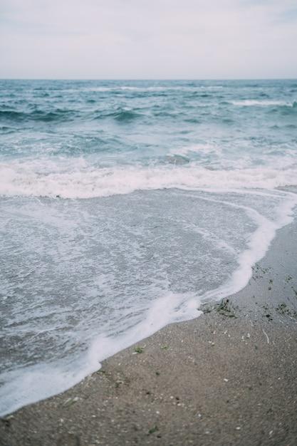 Morze Z Falami Rozbijającymi Się O Plażę, Tworząc Morski Spray. Darmowe Zdjęcia