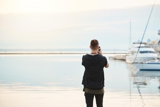 Morze Zapiera Dech W Piersiach. Widok Z Tyłu Strzał Stylowego Młodego Europejczyka W Modnych Ubraniach Stojącego Nad Brzegiem Morza, Fotografującego Morze I Piękny Jacht Na Smartfonie, Będącego Fotoreporterem Lub Amatorem Darmowe Zdjęcia