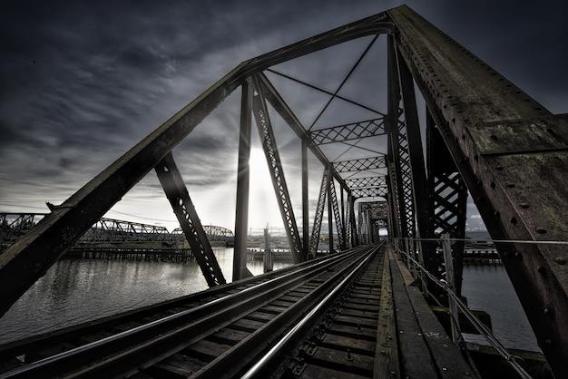 Most Vierendeel Z Tory Kolejowe W Pobliżu Jeziora I Zapierające Dech W Piersiach Słońce świeci Na Ciemnym Niebie Darmowe Zdjęcia