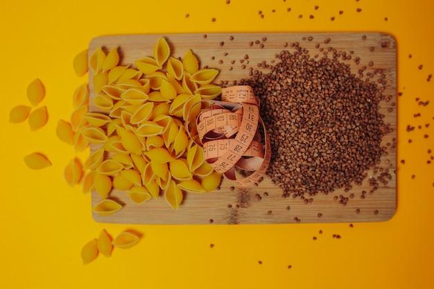 Motyw Diety I Odchudzania. Gryka, Produkty Makaronowe I Taśma Miernicza Na Drewnianej Desce Do Krojenia. Wolne Węglowodany. Premium Zdjęcia