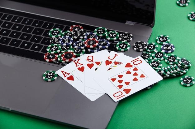 Motyw Kasyna Pokerowego Online. żetony Do Gry, Karty Do Gry Anf Laptop Na Zielonym Tle. Premium Zdjęcia