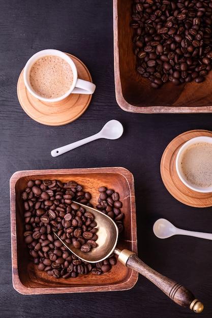 Motyw Kawowy. Gorące Filiżanki Kawy I Talerz Z Ziaren Kawy Na Czarny Drewniany Stół. Premium Zdjęcia