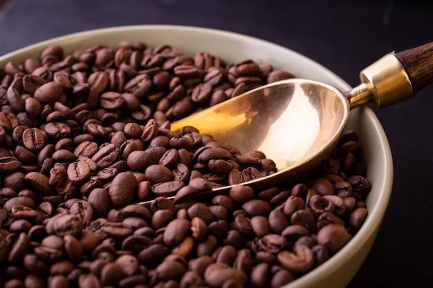 Motyw Kawowy. Talerz Z Ziaren Kawy Na Czarnym Drewnianym Stole. Premium Zdjęcia