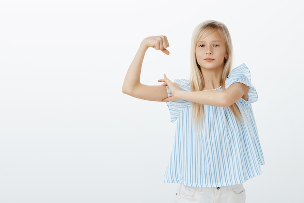 Może Jestem Mały, Ale Silny. Portret Dumnej Pewnej Siebie Młodej Blondynki W Stylowej Bluzce, Podnoszącej Rękę I Pokazującej Mięśnie, Mówiącej O Sile, Pewnej Siebie I Zadowolonej Na Szarej ścianie Darmowe Zdjęcia