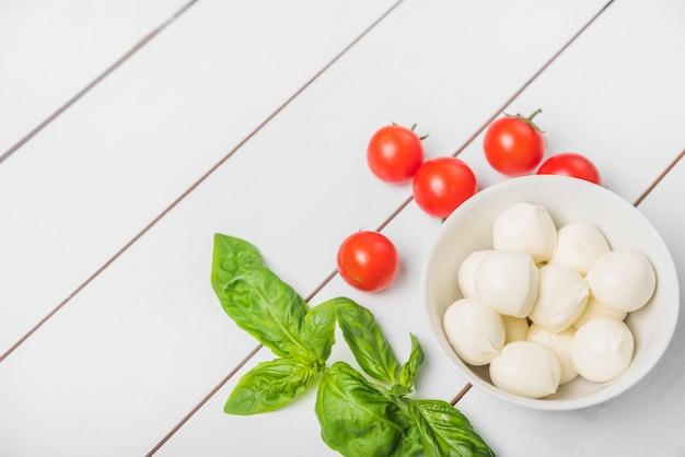 Mozzarella Serowa Piłka Z Basilu Liściem I Czerwonymi Pomidorami Na Drewnianym Białym Tle Darmowe Zdjęcia