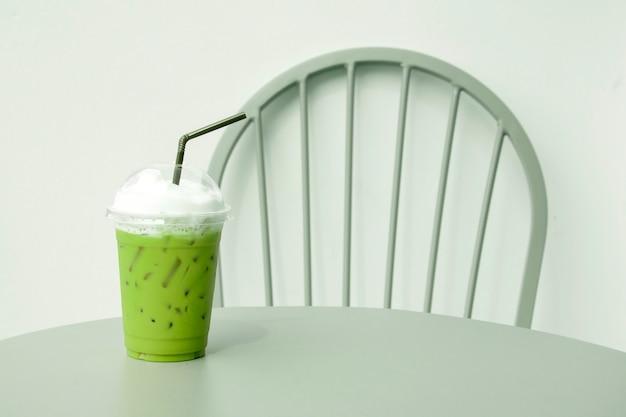 Mrożona Zielona Herbata Ze Słomką W Plastikowym Kubku Na Stole. Premium Zdjęcia