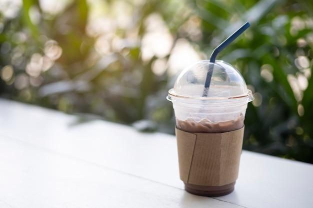 Mrożone Kakao W Plastikowym Kubku Na Zielonym Tle Tabeli Premium Zdjęcia