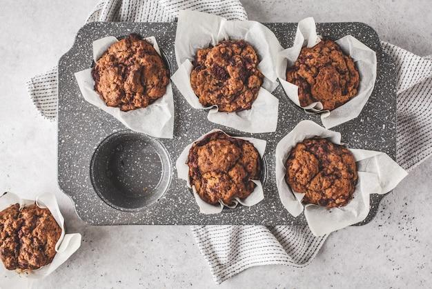 Muffiny Jagodowe Zdrowe Wegańskie W Naczyniu Do Pieczenia Na Białym Tle. Premium Zdjęcia