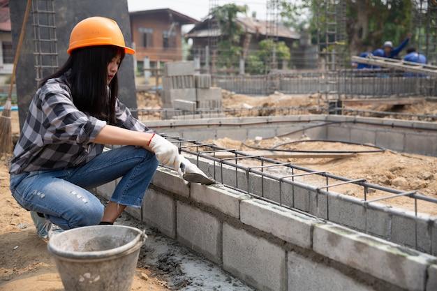 Murarz Pracownik Instaluje Ceglanego Kamieniarstwo Na Zewnętrznej ścianie Z Kielni Kitu Nożem Darmowe Zdjęcia