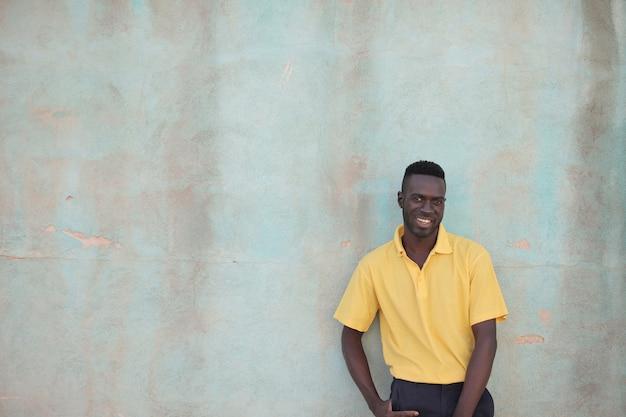 Murzyn W żółtej Koszuli Uśmiechnięty Za ścianą Darmowe Zdjęcia