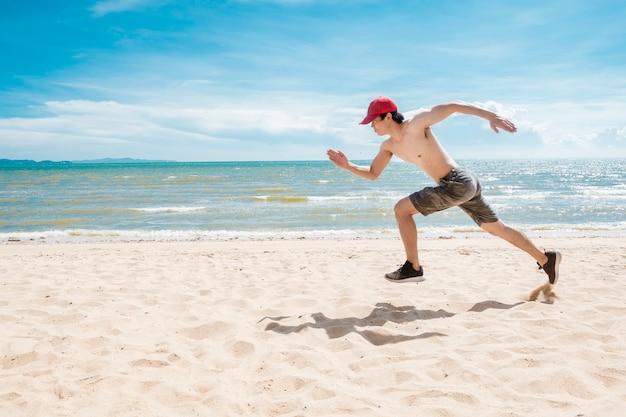Muskularny mężczyzna biegnie po plaży Premium Zdjęcia