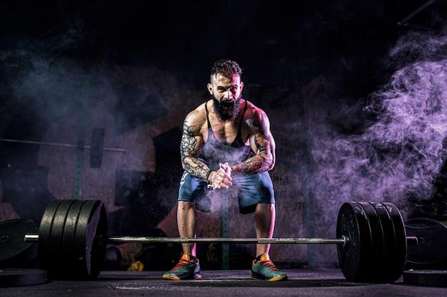 Muskularny Mężczyzna Fitness Przygotowuje Się Do Martwego Ciągu Sztangi W Nowoczesnym Centrum Fitness. Trening Funkcjonalny. Premium Zdjęcia