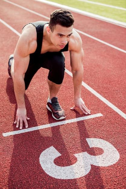 Muskularny mężczyzna młody biegacz na linii startu Darmowe Zdjęcia