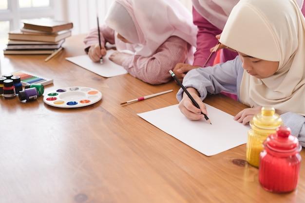 Muzułmanka uczy swoje dzieci malowania i rysowania w domu. Premium Zdjęcia