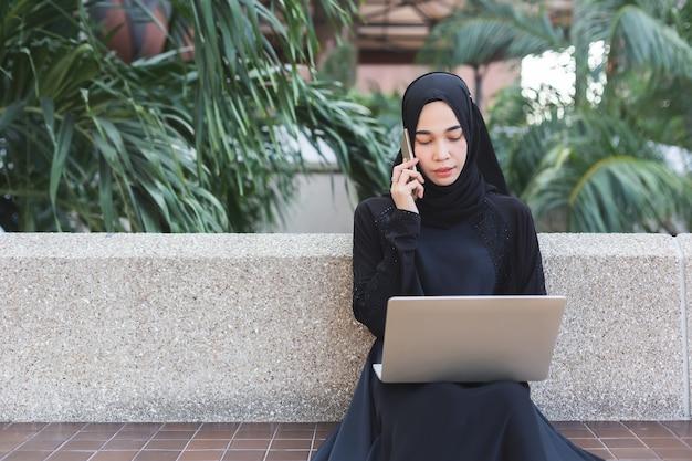 Muzułmańska Kobieta Opowiada Telefon I Pracuje Z Laptopu Plenerowym Biurem W Czarnym Hijab. Premium Zdjęcia