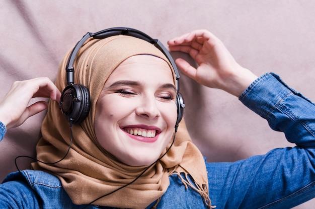 Muzułmańska kobieta słucha muzyka na hełmofonach Darmowe Zdjęcia
