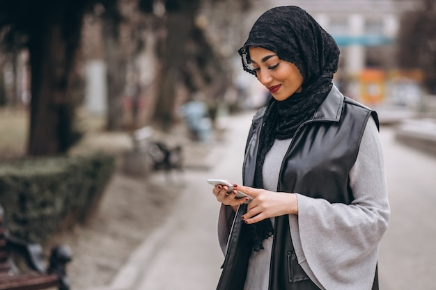 Muzułmańska kobieta używa telefon na zewnątrz w ulicie Darmowe Zdjęcia
