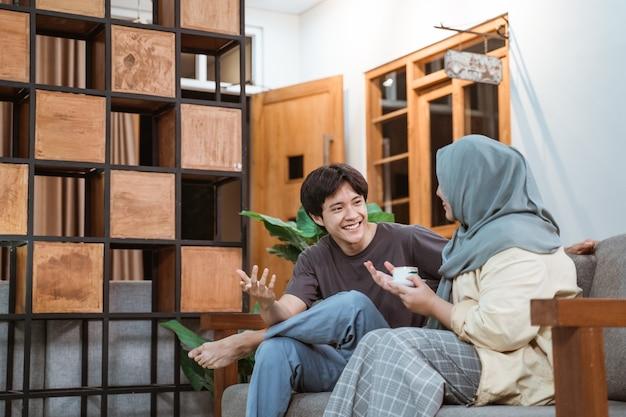 Muzułmańska Młoda Para Rozmawia Na Kanapie W Domu Premium Zdjęcia