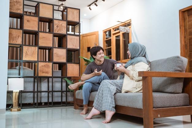 Muzułmańska Młoda Para Rozmawia Na Kanapie W Salonie W Domu Premium Zdjęcia