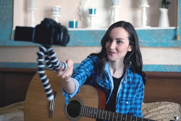 Muzyk z gitarą akustyczną na łóżku sam nagrywa Premium Zdjęcia