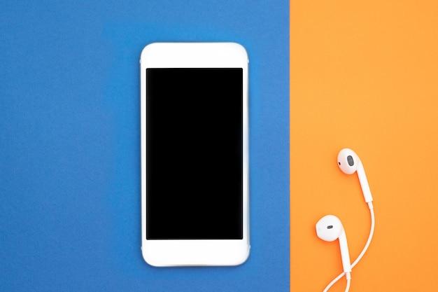 Muzyka, gadżety, miłośnik muzyki. biały smartfon i słuchawki na pomarańczowym i niebieskim tle ze słuchawkami. widok z góry. leżał płasko, widok z góry. Premium Zdjęcia