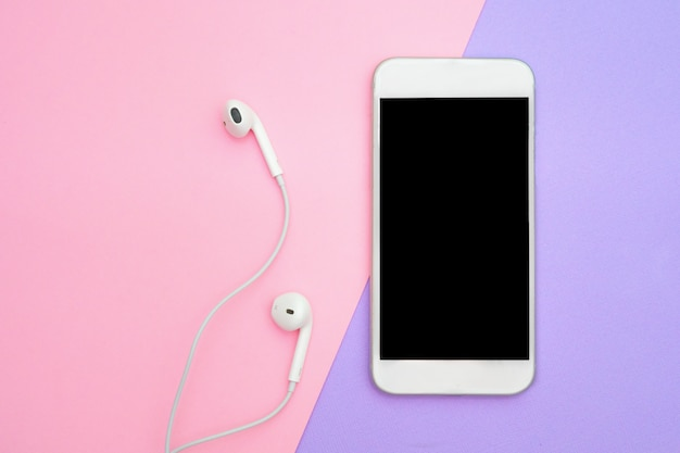 Muzyka, gadżety, miłośnik muzyki. biały smartfon na fioletowym i niebieskim tle ze słuchawkami. widok z góry. leżał płasko, widok z góry Premium Zdjęcia