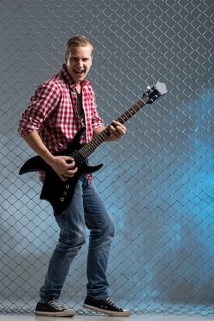 Muzyka. Młody Muzyk Z Gitarą Na ścianie Ogrodzenia Darmowe Zdjęcia