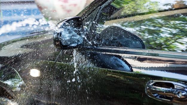 Mycie czarnego samochodu wodą pod wysokim ciśnieniem. Premium Zdjęcia