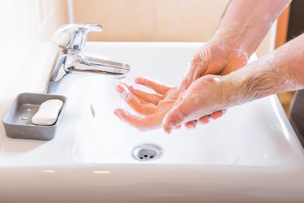 Mycie Rąk Człowieka Płukanie Mydłem Pod Bieżącą Wodą Przy Zlewie, Higiena Rąk Zapobieganie Koronawirusowi Premium Zdjęcia
