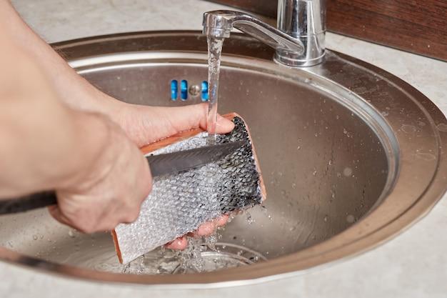 Mycie Rąk I Czyszczenie Ryb łososiowych Nad Zlewem Kuchennym Premium Zdjęcia