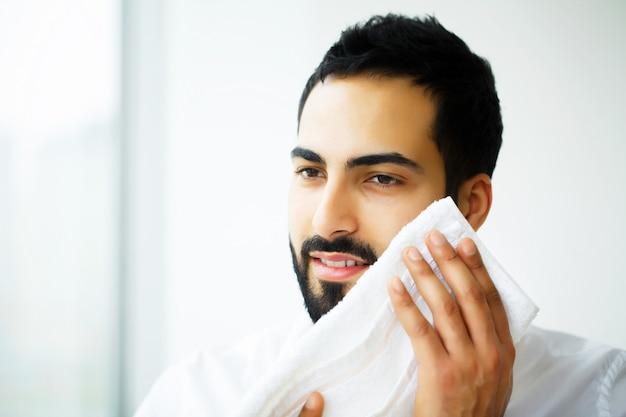 Mycie twarzy szczęśliwy człowiek suszenia skóry ręcznikiem Premium Zdjęcia