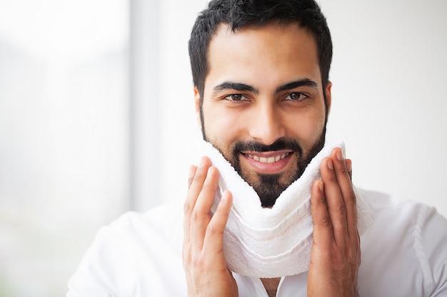 Mycie twarzy. szczęśliwy człowiek suszenia skóry z ręcznikiem Premium Zdjęcia