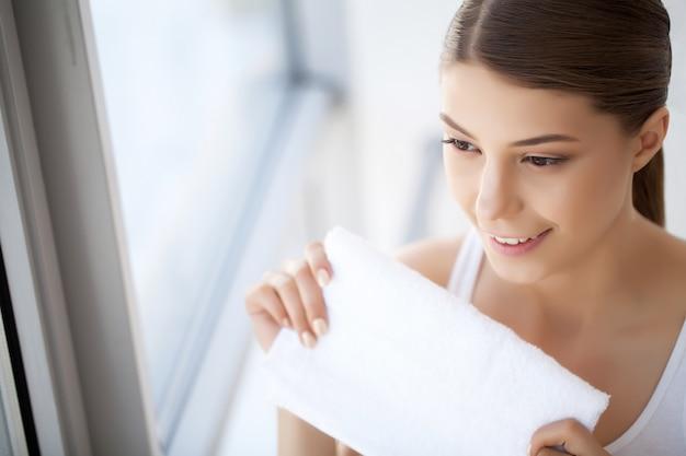 Mycie twarzy zbliżenie szczęśliwej kobiety susząca skóra z ręcznikiem. wysoka rozdzielczość Premium Zdjęcia