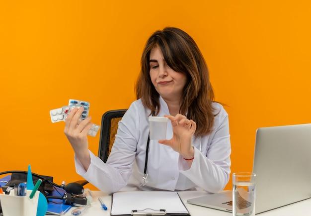 Myśląca Kobieta W średnim Wieku Ubrana W Szlafrok Medyczny Ze Stetoskopem Siedząca Przy Biurku Praca Na Laptopie Z Narzędziami Medycznymi Trzymająca Pustą Puszkę Z Tabletkami Na Odizolowanej Pomarańczowej ścianie I Patrząc Na Nią Darmowe Zdjęcia