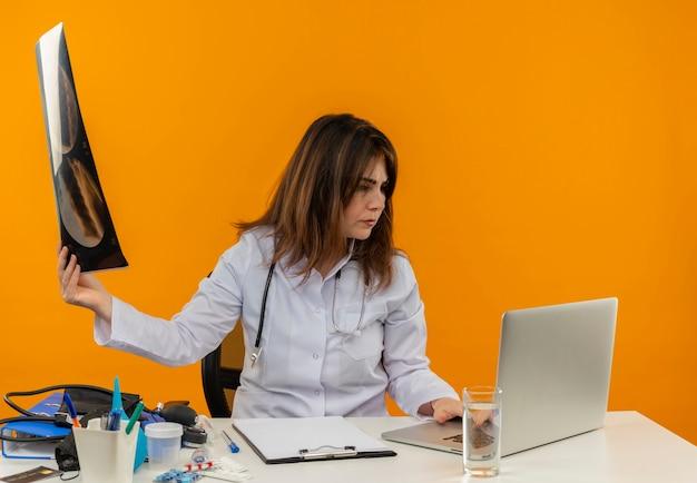 Myślący Lekarz W średnim Wieku W Szlafroku Medycznym Ze Stetoskopem Siedzący Przy Biurku Na Laptopie Z Narzędziami Medycznymi Trzymającymi Prześwietlenie I Patrząc Na Laptopa Na Odizolowanej Pomarańczowej ścianie Darmowe Zdjęcia