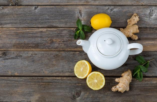 Na drewnianym stole jest biały czajniczek, cytryna, liście mięty i imbir. wolne miejsce na tekst Premium Zdjęcia
