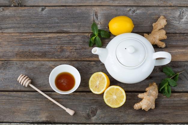 Na drewnianym stole jest biały czajniczek, cytryna, miód, liście mięty i imbir. wolne miejsce na tekst Premium Zdjęcia