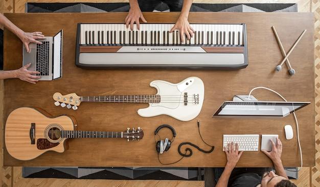 Na Drewnianym Stole Znajdują Się Klawisze Muzyczne, Gitara Akustyczna, Gitara Basowa, Mikser, Słuchawki, Komputer Oraz Pałeczki Perkusyjne. Darmowe Zdjęcia
