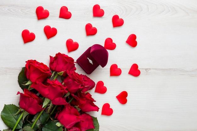 Na Jasnym Drewnianym Stole Czerwone Róże, Dekoracje W Formie Serc I Pierścionek Zaręczynowy Premium Zdjęcia