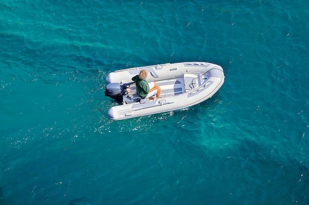 Na Lazurowym Morzu Powoli Płynie Ponton Z Silnikiem. Rejs Statkiem W Słoneczny Letni Dzień. Premium Zdjęcia