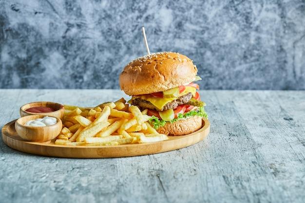 Na Marmurowym Stole Drewniany Talerz Pełen Burgera, Smażonego Ziemniaka Z Keczupem I Majonezem. Darmowe Zdjęcia