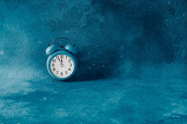 Na Retro Budziku Za Pięć Minut Do Północy. Pięć Minut Przed Rozpoczęciem Nowego Dnia Lub Nowego Roku. Końcowe Odliczanie. Stonowany W Klasycznym Modnym Niebieskim Kolorze. Copyspace. Premium Zdjęcia
