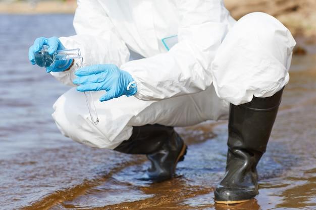 Na Rysunku W Zbliżeniu Przedstawiono Chemika W Ochronnej Odzieży Roboczej Oraz Rękawiczkach Trzymających Kolbę I Badającego Wodę W Rzece Premium Zdjęcia